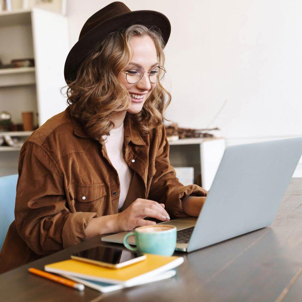 image-of-cheerful-woman-working-with-laptop-while-CNX4RJP.jpg